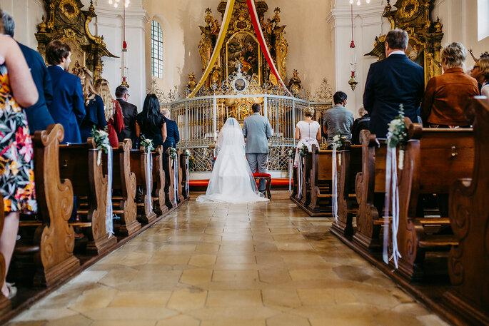 Das Brautpaar vor dem Traualtar, Foto von Hüttner Fotografie.