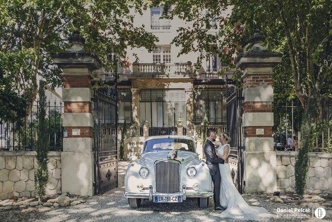Deux mariés enlacés à côté d'une voiture de collection blanche, devant le portail du Château la Beaumetane