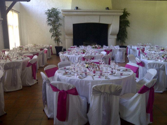 La salle de réception du Domaine des Etoiles et sa grande cheminée au style d'époque. Devant sont dressées des tables pour la réception du mariage.