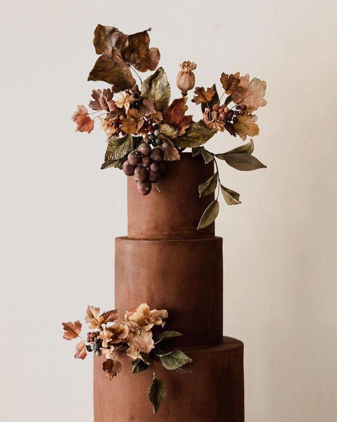 Hochzeitstorte in Braun mit getrockneten Blättern als Verzierung