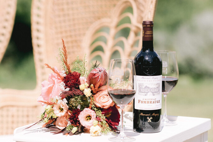 Deux verres du vin du Château Fombrauge servis à côté d'un bouquet de mariée, le tout disposé sur une table