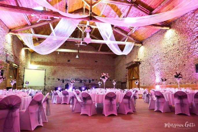 Un dîner de mariage a lieu dans une grange décorée avec poutres et pierres apparentes