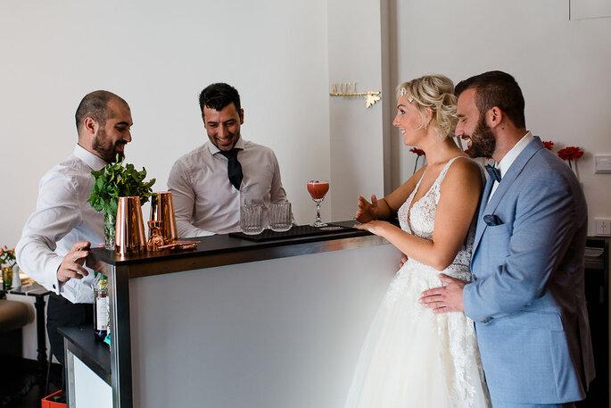 Das Brautpaar steht am Tresen von Two guys and a bar und bestellt Cocktails.