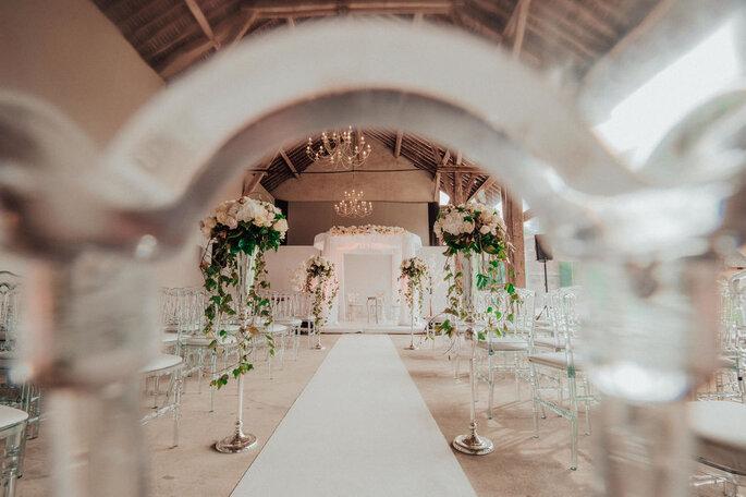 Une cérémonie laïque est organisée en intérieur avec une grande arche blanche, des hauts vases remplis de fleurs, un tapis blanc pour un style champêtre-rustique