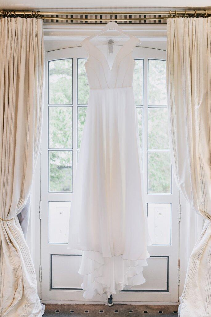Une robe de mariée pendue à une tringle à rideaux