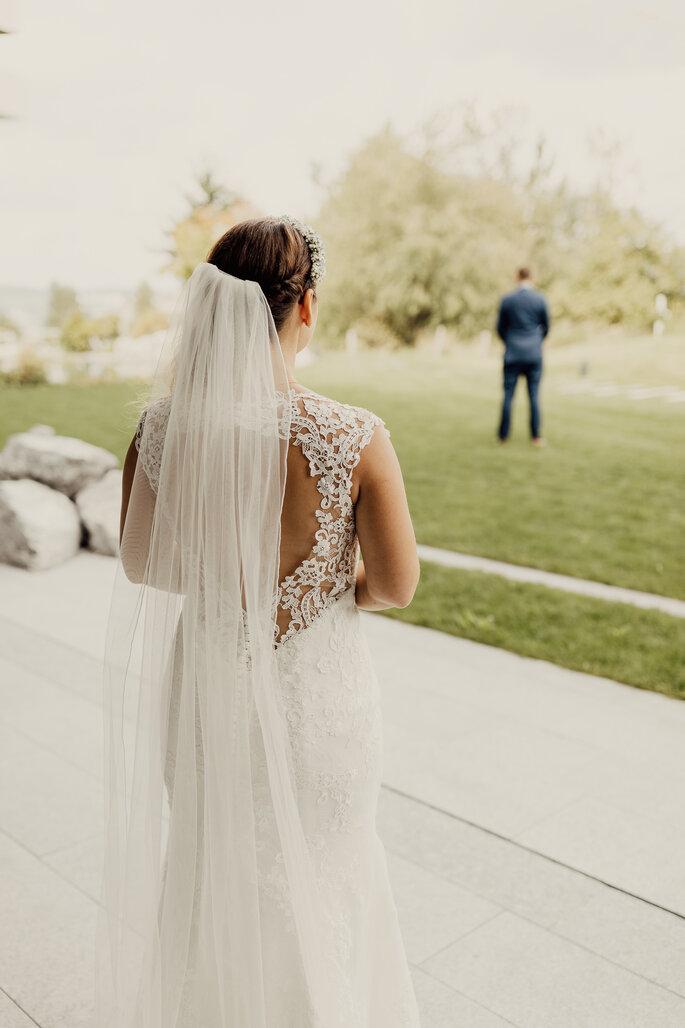 Brautkleid mit Rückenausschnitt. Braut von hinten zu sehen. Ihr gegenüber mit Rücken zu ihr der Bräutigam