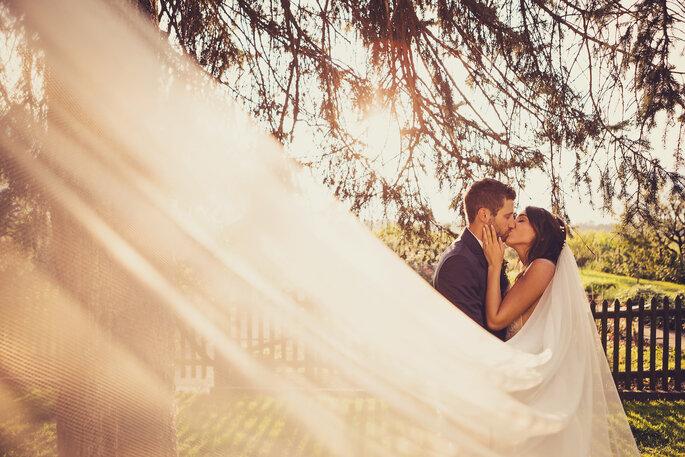 Hochzeitsfoto. Brautpaar küsst sich, Schleier der Braut weit aufgefächert