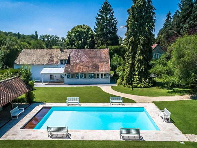Un corps de bâtiment rustique avec une piscine en son centre, dans un superbe parc arboré bien entretenu