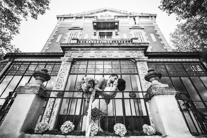 Deux mariés s'embrassant devant la façade du Château de Beaumetane