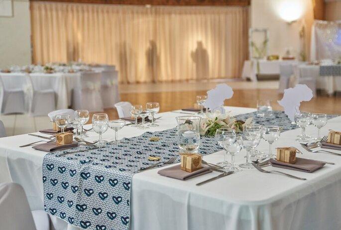 Une table décorée pour un repas de mariage avec des petits cadeaux pour les invités à chaque place.