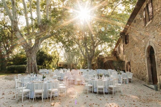 Des tables dressées dans un parc ombragé longé d'une bâtisse en pierres d'époque