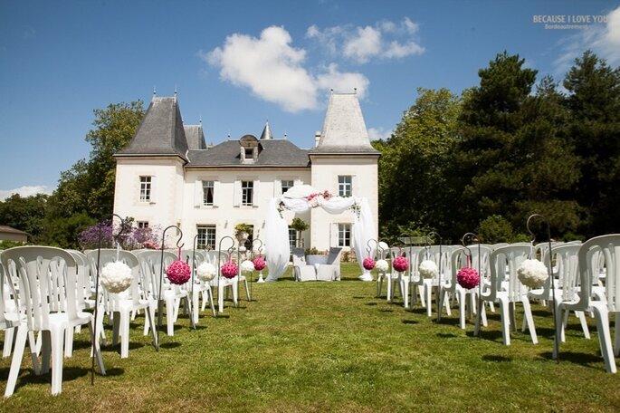 Des rangs de chaises blanches disposées devant le Château du Domaine de la Pinelais