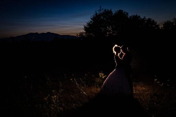 Un couple de mariés enlacés à la tombée de la nuit