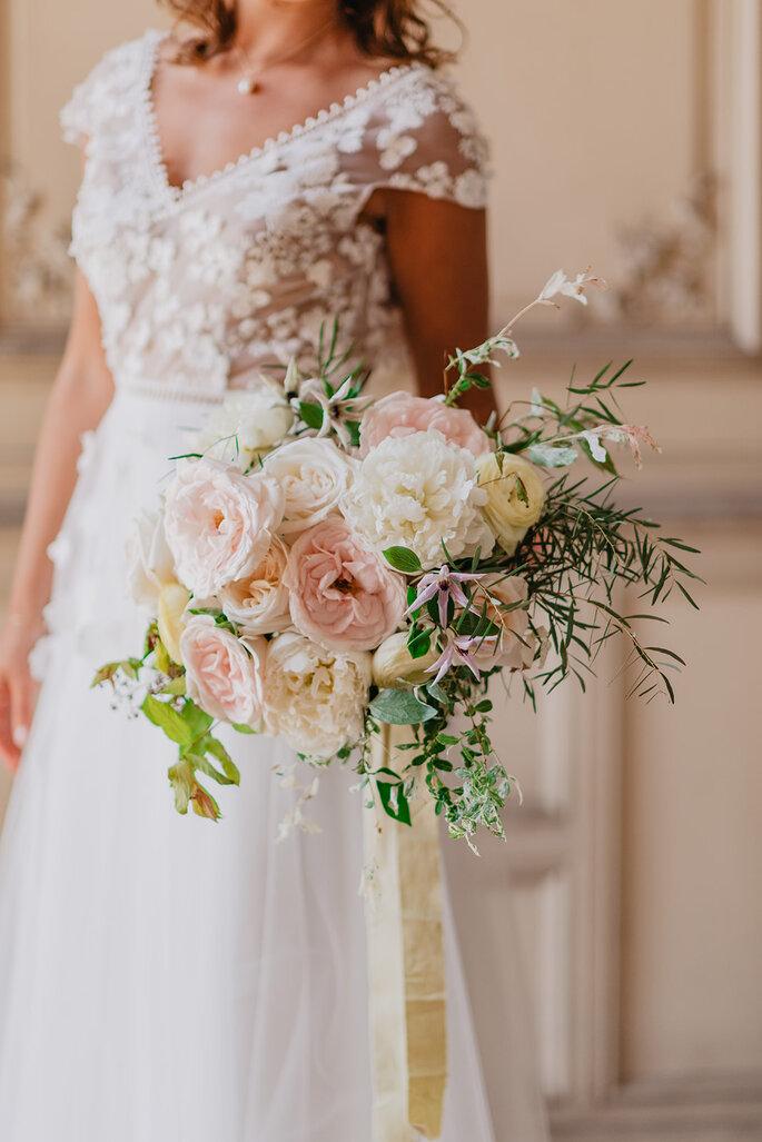 Une mariée avec son bouquet aux tons pastels réalisé par un wedding planner et fleuriste designer