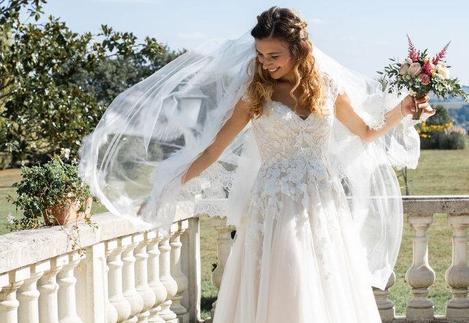 Une mariée en train de sourire et de jouer avec son voile sur un balcon, un bouquet à la main