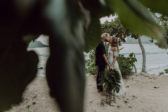 Das Brautpaar küsst sich am Strand, vor der Linse sind grüne Blätter zu sehen.