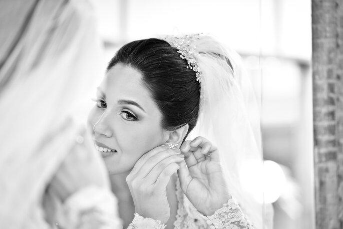 Noiva se arruma e coloca brincos em frente ao espelho