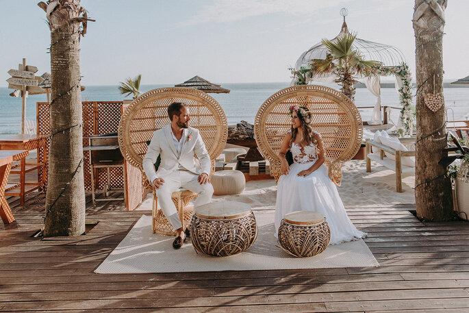 noivos praia sentados em cadeirões de palha