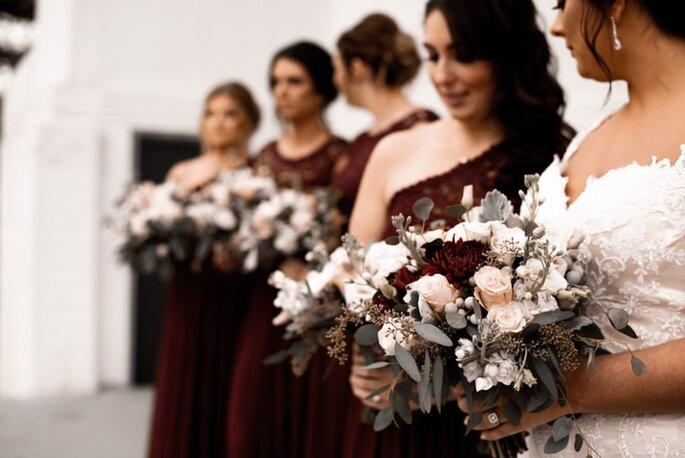 damas de honor con el mismo bouquet de flores y el mismo vestido vino