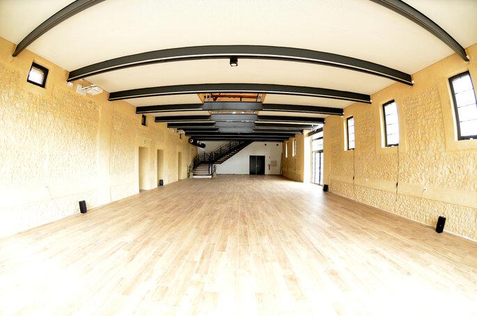 Salle de réception avec charpentes en bois apparentes.