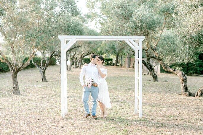Deux mariés sous une arche en bois blanche au milieu d'oliviers, en train de s'enlacer avant leur cérémonie