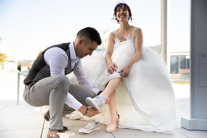 Le futur marié enlève les baskets de sa femme pour lui faire passer des chaussures à talons beige