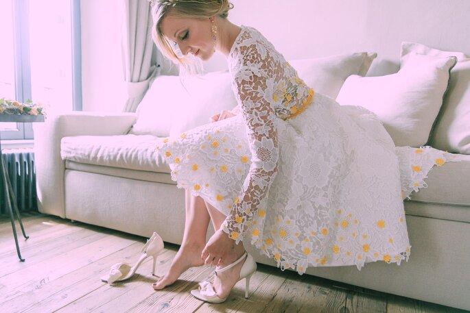 Die Braut zieht ihre Schuhe an.