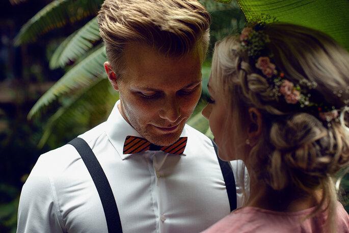 Ein Brautpaar liegt sich in einem grünen Garten zärtlich in den Armen und lächelt dabei.