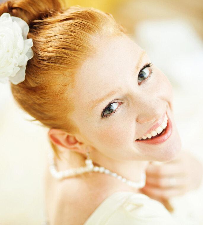 Pelo recogido adornado con una flor blanca. shutterstock_112597286
