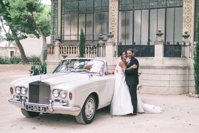 Deux mariés avec une voiture de collection devant la façade du Château de Beaumetane