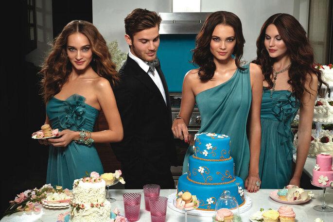 Drei Frauen in blauen Kleidern und ein Mann bedienen sich an dem Buffet