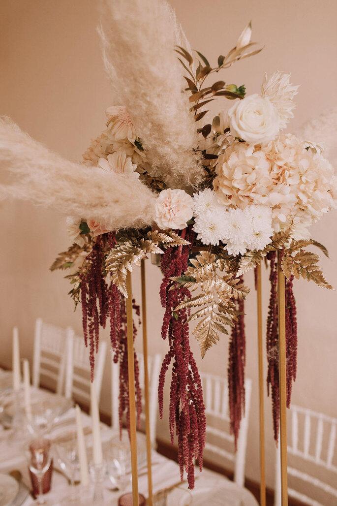 Un superbe bouquet de fleurs blanches et ocres orne une table de mariage