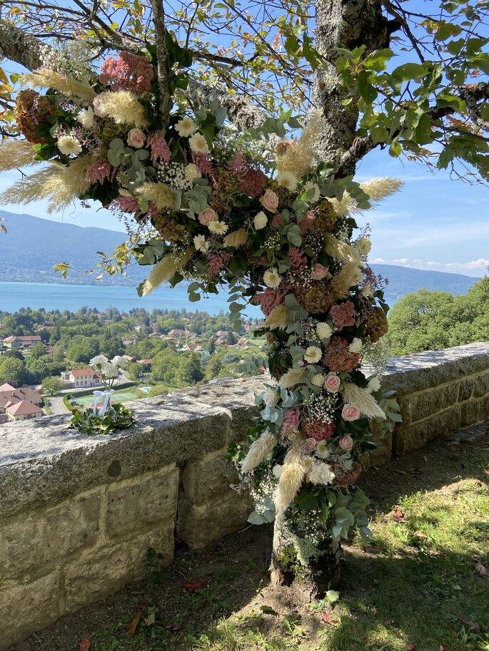 Décoration florale majestueuse dans un arbre pour un mariage avec vue sur un lac