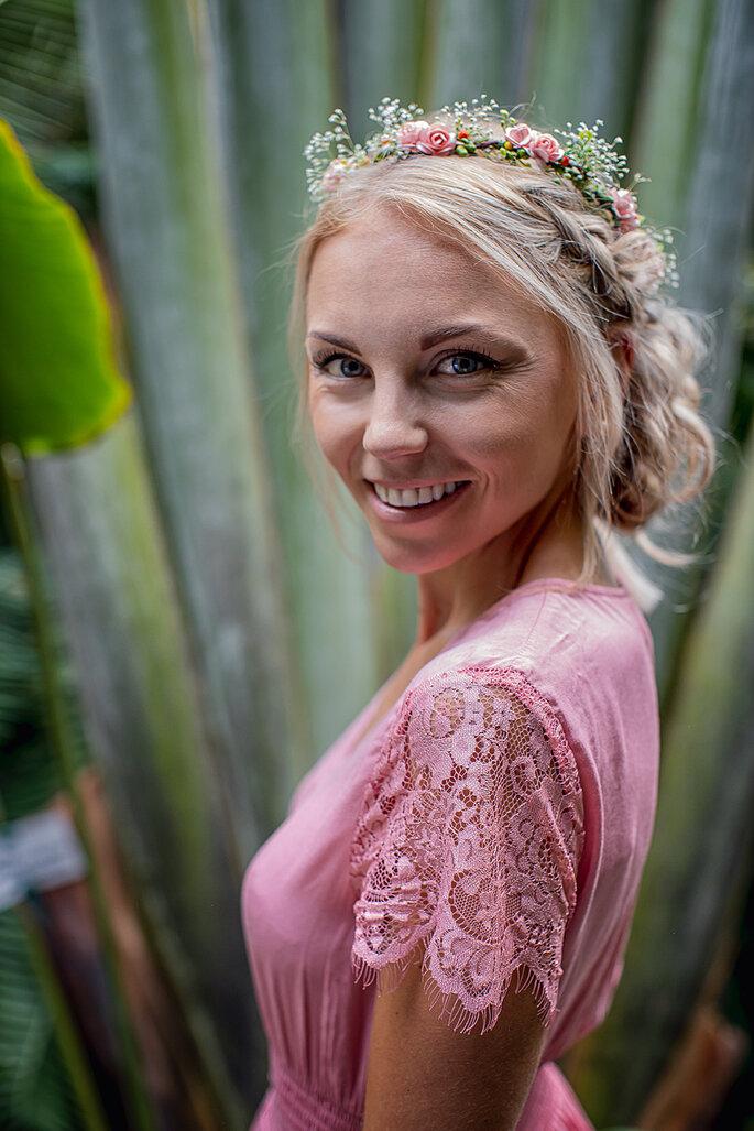 Die Braut trägt ein rosa Kleid und hat ihre geflochtene Frisur selbst gemacht. Dazu trägt sie einen zarten Blumenkranz im Haar.