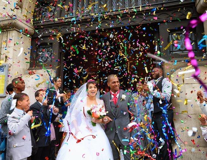Des mariés sortent de l'église et sont photographiés sous une pluie de confettis que jettent leurs invités