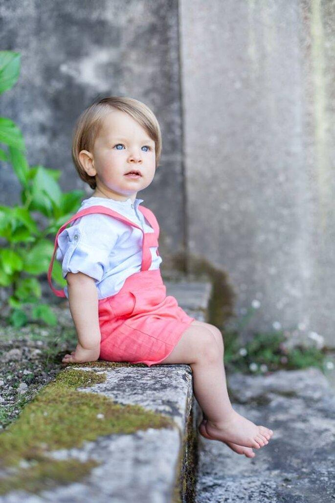 menino louro e de olhos azuis com calções rosa tiroles