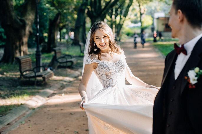 Eine Braut lacht im Park in eine Kamera.