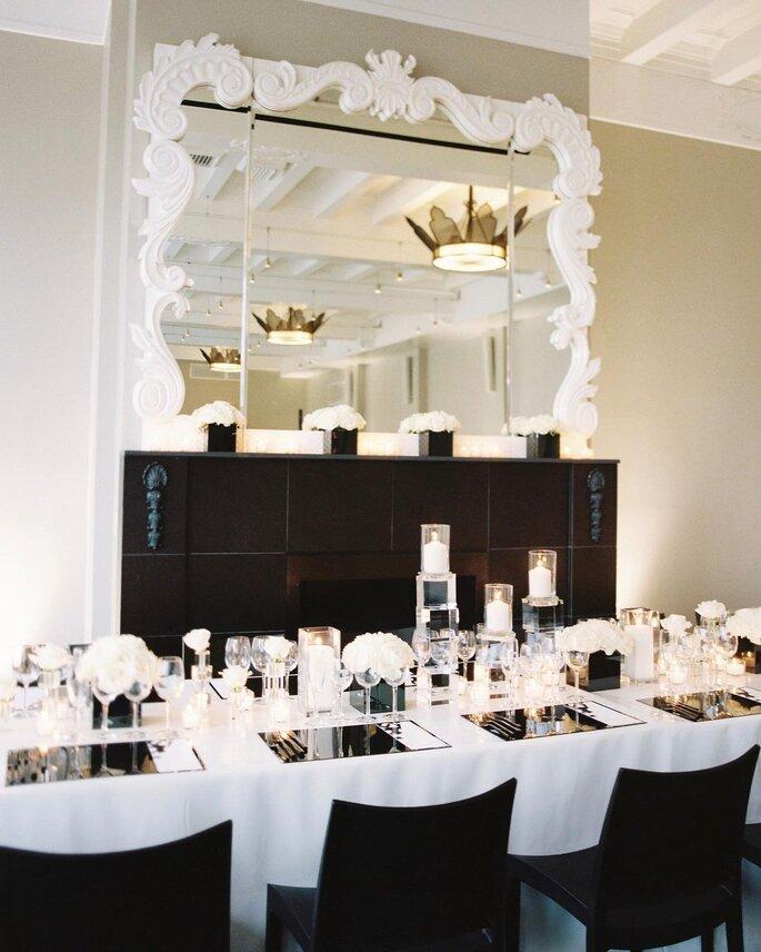 Decoración para banquete de boda minimalista elegante con colores negro y blanco con detalles plateados y manteles de espejo y centro de mesa de velas