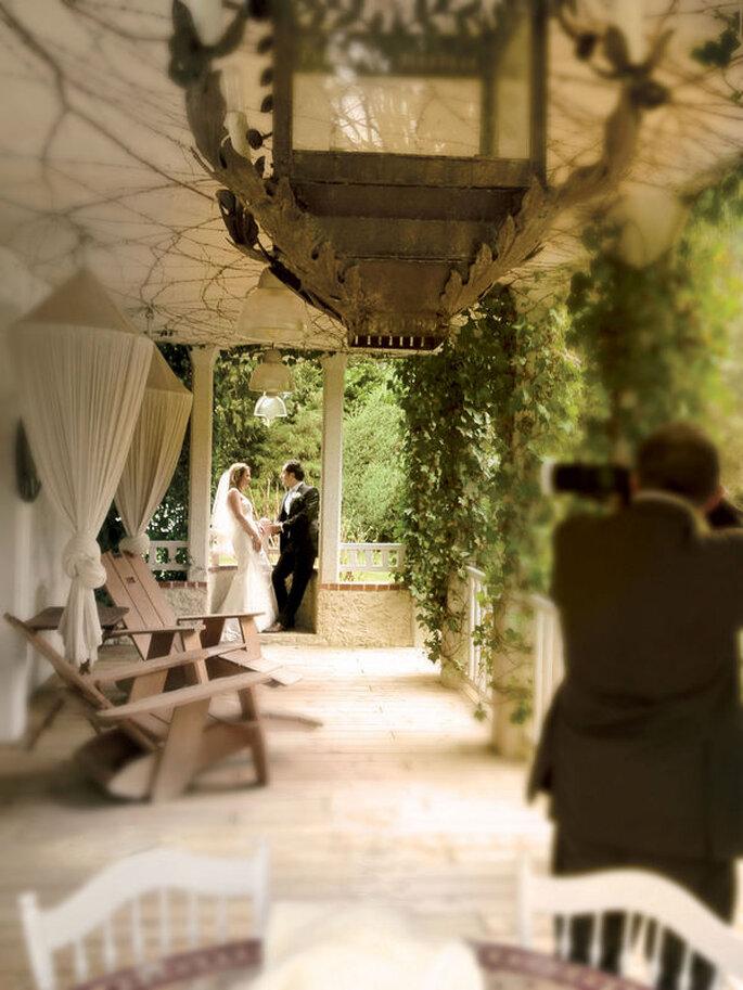 Un couple de mariés assis sur le rebord d'une terrasse rustique est en train de se faire photographier