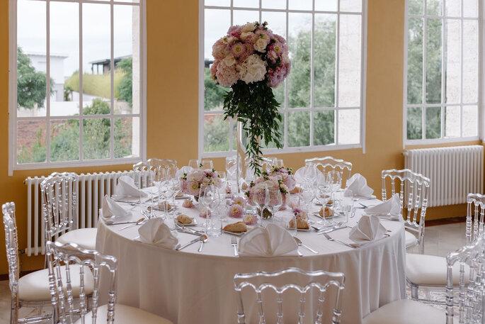 Une table d'un banquet de réception de mariage au tons roses, dans une salle lumineuse aux grandes baies vitrées