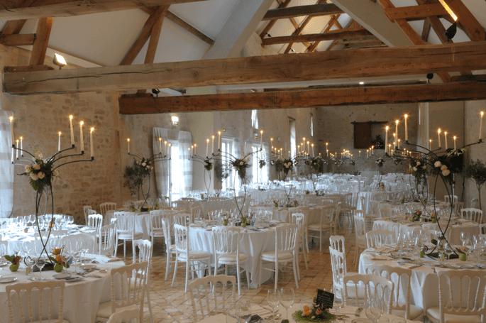 La salle de réception du Château de Serans avec ses charpentes apparentes. Des tables sont installées pour le dîner de réception.