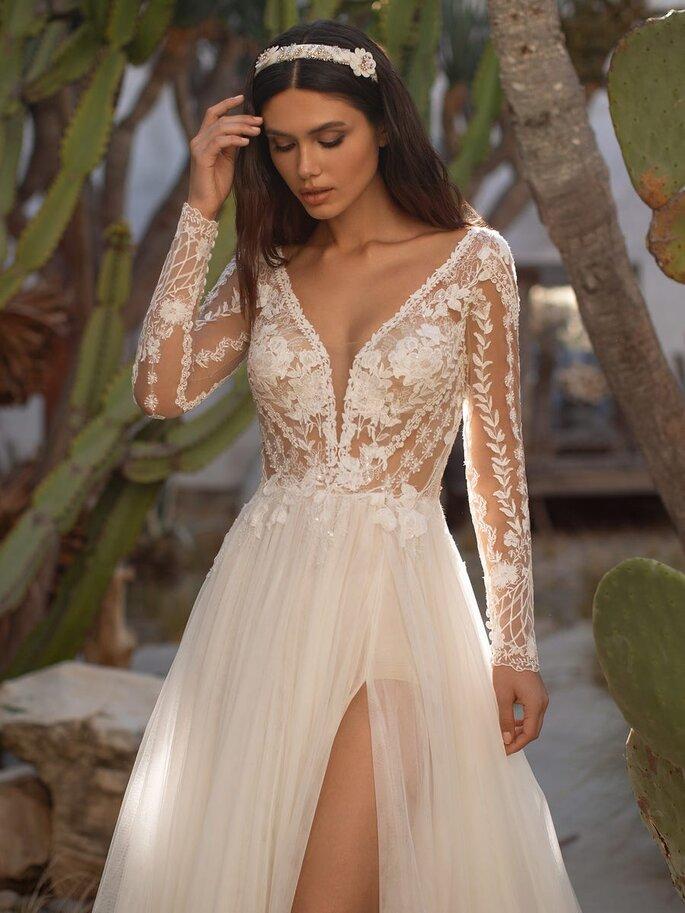 Vestido de novia con falda de tul y mangas largas de encaje con apertura por la pierna de Pronovias