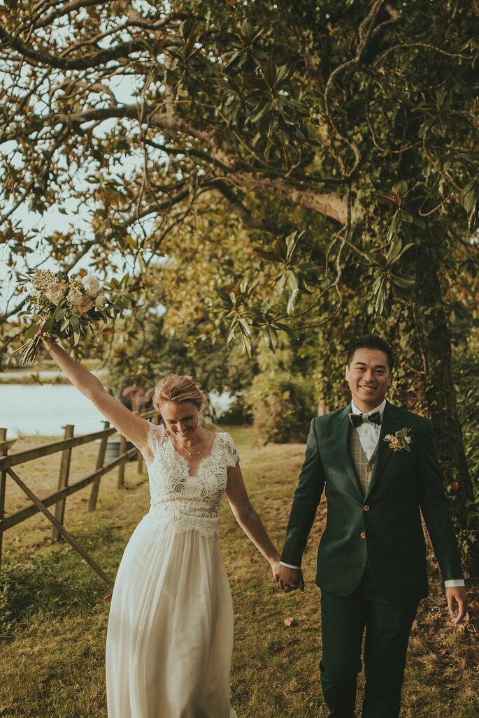 Un couple de mariés se tenant la main dans un décor naturel.