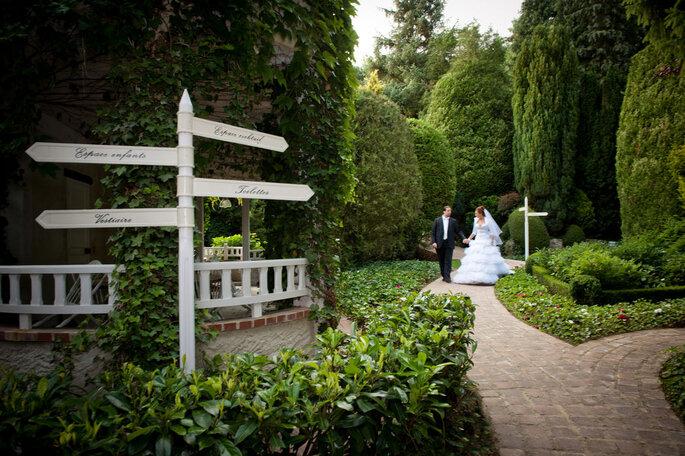 Un couple de mariés se promène main dans la main dans un magnifique parc paysager