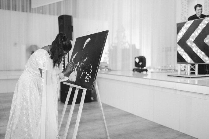 L'artiste Sharuki en train de peindre un portait sur une toile