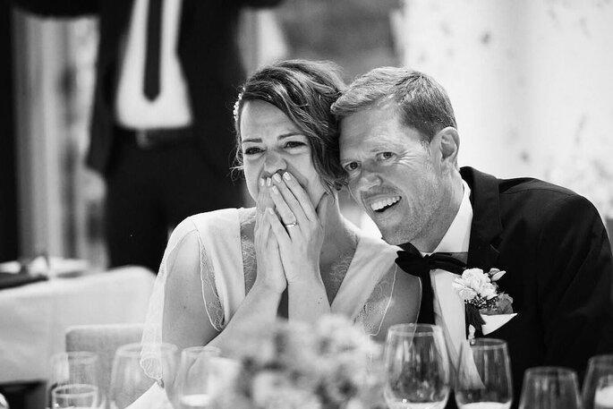 Ein Brautpaar hält sich in den Armen, lächelt und hat Tränen in den Augen.