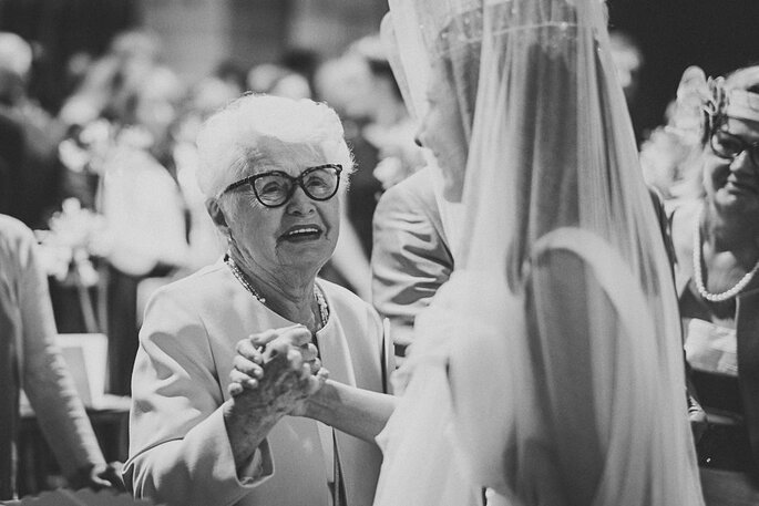 Une grand-mère émue regarde la mariée en lui tenant la main