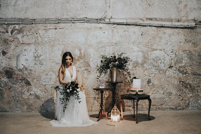 noiva com parede rústica por detrás mesa com arranjos silvestres lanternas design industrial