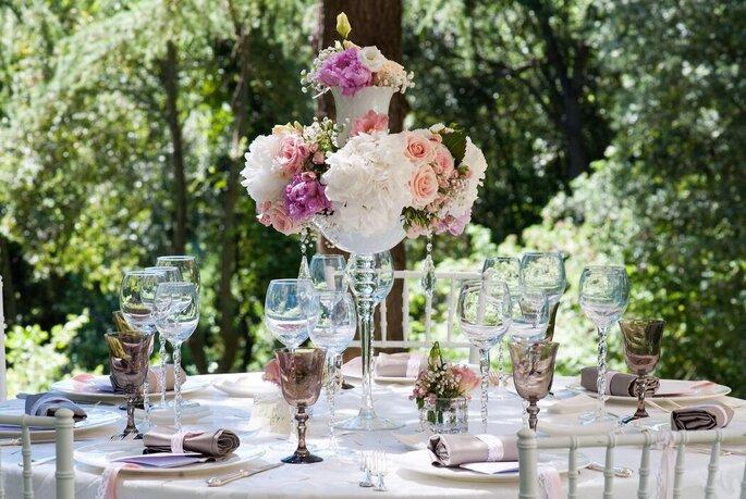 Une table dressée dans un jardin avec une superbe composition de fleurs pour un mariage