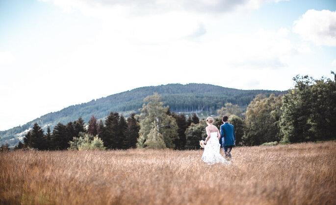 Photo de mariés dans un champ de dos